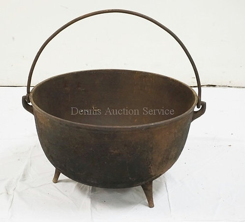 CAST IRON CAULDRON WITH A SWING HANDLE. 22 INCH DIA.