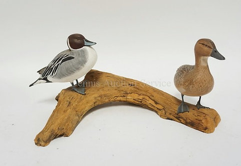 NELSON & PHYLLIS WOODEN FIGURE WITH CARVED DUCKS STANDING ON A LOG. 14 1/4 INCHE