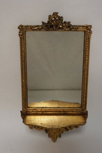 MIRROR IN A CARVED GILTWOOD FRAME WITH SHELF. 17 1/2 IN X 91N OVERALL DIMENSIONS