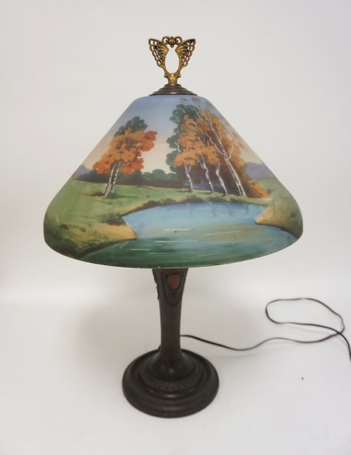 REVERSE PAINTED TABLE LAMP WITH AN ORNATE WHITE METAL BASE HAVING A BRONZE FINIS