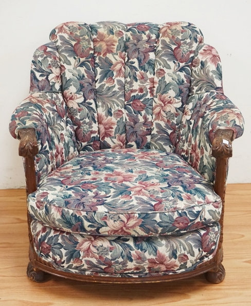 UPHOLSTERED LOUNGE CHAIR WITH A CARVED FRAME. 34 INCHES WIDE. 32 INCHES HIGH.