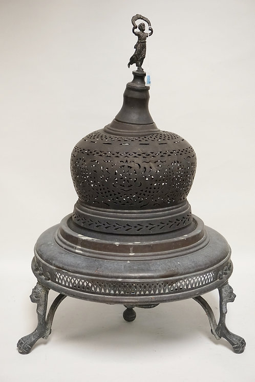 BRASS ROOM HEATER WITH LION FACES AND PAW FEET, A FIGURAL FINIAL, AND DECORATIVE