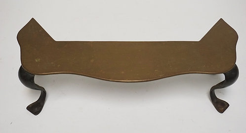 BRASS & IRON FIREPLACE TRIVET. 18 1/2 INCHES WIDE. 5 INCHES HIGH.