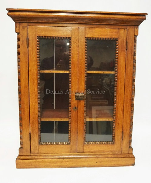OAK HANGING CABINET WITH SPOOL TURNED QUARTER COLUMNS AND CARVED TRIM ON THE DOO