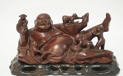 CARVED WOODEN RECLINING BUDDHA WITH SEVERAL FIGURES CLIMBING ON HIM. MISSING ONE