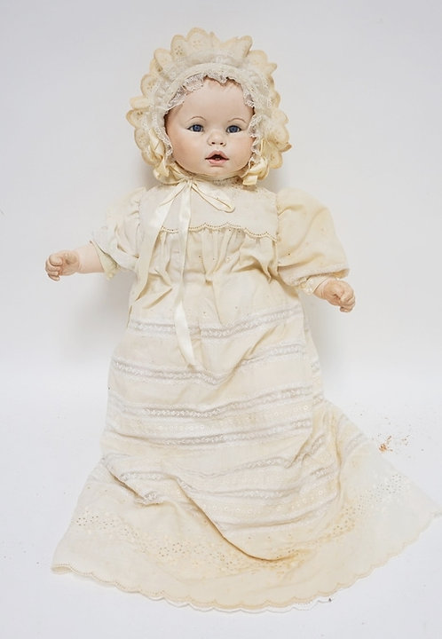 BISQUE HEADED BABY DOLL MEASURING 21 INCHES LONG.