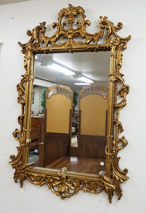 MIRROR WITH AN ORNATE GOLD PAINTED FRAME. 54 X 34 1/2 INCHES.