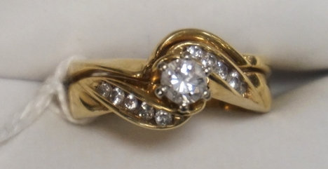 14K GOLD DIAMOND RING. 1/4 CARAT MAIN STONE FLANKED BY CHANNEL SET DIAMOND ACCEN