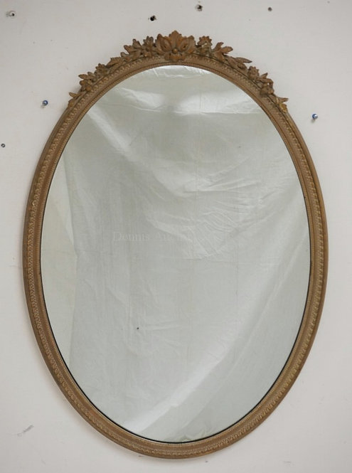 OVAL MIRROR WITH A FLORAL CARVED CREST. HAS A CHIP. 37 1/2 X 26 INCHES.
