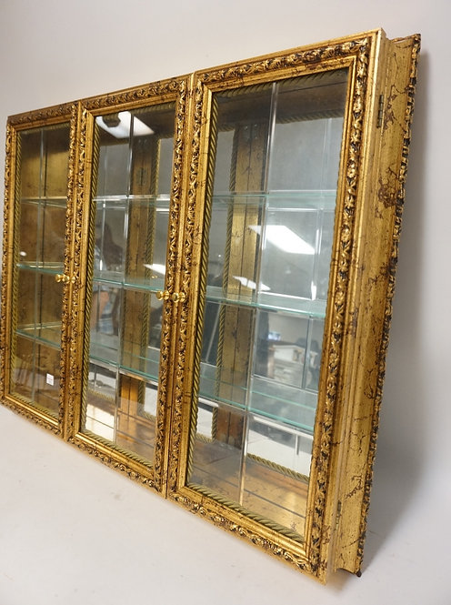 GILT HANGING DISPLAY CABINET WITH MIRROR BACK AND GLASS SHELVES. 29 IN X 23 1/2