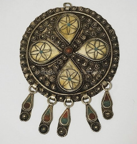 NORTH AFRICAN DISK PENDANT WITH INSET STONE AND BONE DECORATIONS. 4 INCH DIA.