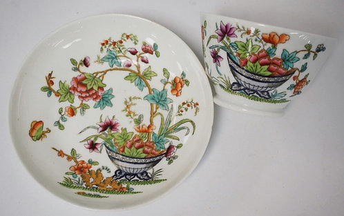 ANTIQUE HANDLELESS CUP AND SAUCER WITH HAND ENAMELED DECORATION OF FLOWERS IN A