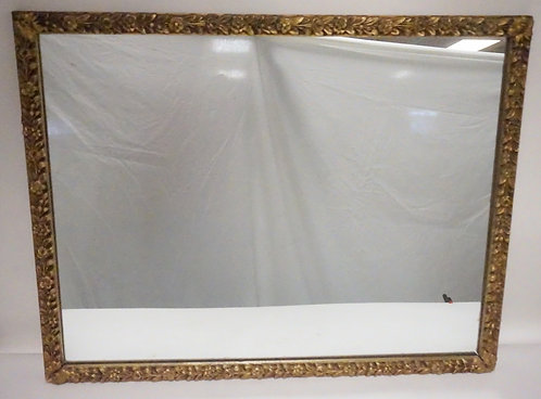 GOLD GILT MIRROR WITH FLOWERS IN DEEP RELIEF. 36 1/2 X 28 3/4 INCHES. HAS A CHIP