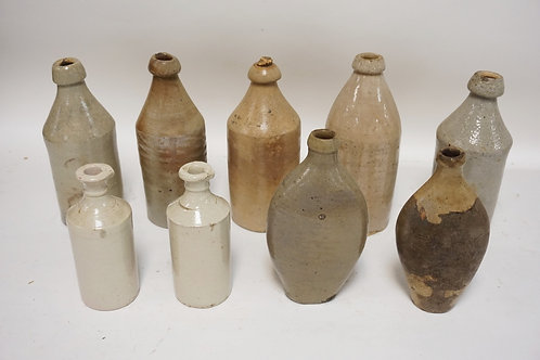 LOT OF 9 PIECES OF STONEWARE. 7 BOTTLES & 2 FLASKS. TALLEST IS 10 1/2 INCHES.