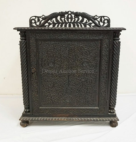 INTRICATELY CARVED ONE DOOR CABINET WITH AN OPENWORK BACKSPLASH. 36 INCHES WIDE.