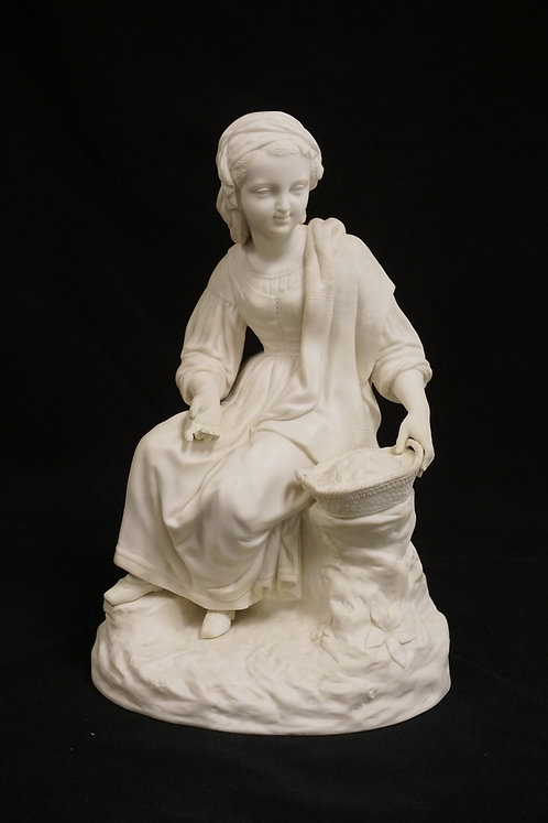 PARIAN PORCELAIN FIGURE OF A SEATED WOMAN WITH A BASKET. 12 5/8 INCHES HIGH.