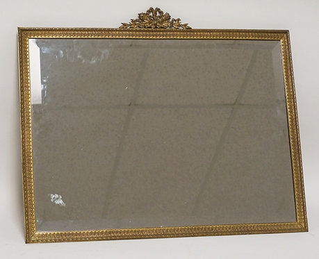 BRONZE FRAMED MIRROR WITH A RIBBON & TORCH CREST. 22 3/4 X 18 3/4 INCHES.