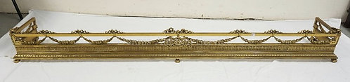 ORNATE BRASS FIREPLACE FENDER WITH FLORAL SWAG AND A WREATH CENTER WITH CROSSED