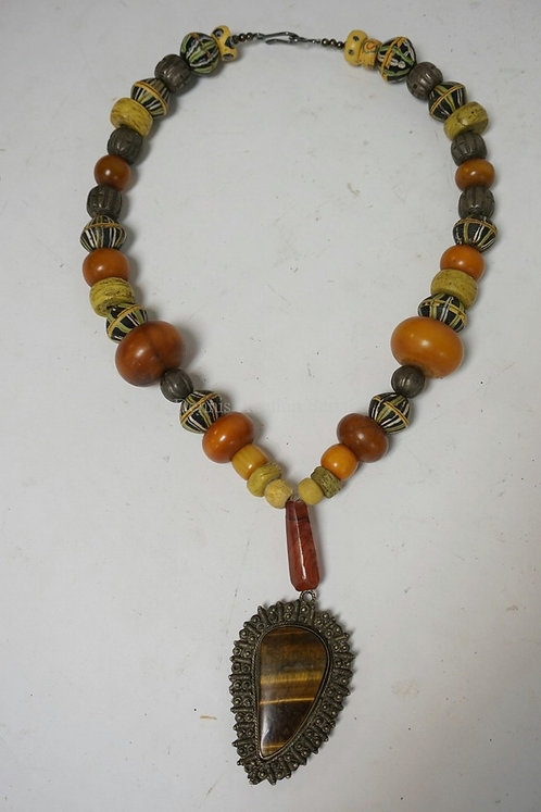 BEADED NECKLACE INCLUDING CARNELIAN, ANTIQUE AMBER, WOULD GLASS, AND SILVER BEAD