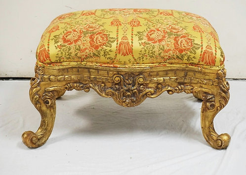 CARVED AND GOLD GILT OTTOMAN WITH FLORAL & TASSEL UPHOLSTERY. 35 X 24 AND 20 1/2