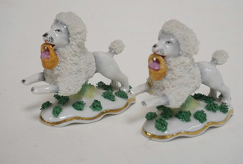 PAIR OF GERMAN PORCELAIN FIGURE OF POODLES WITH BASKETS IN THEIR MOUTHS. 2 1/2 I