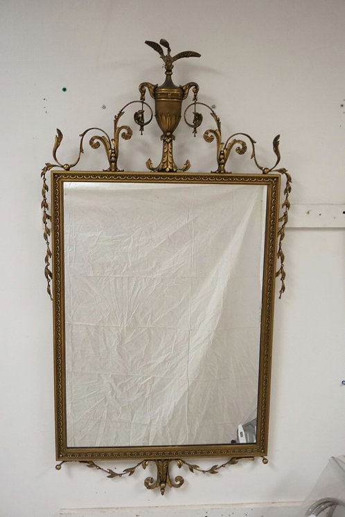 GOLD GILT GESSO MIRROR WITH AN URN CREST. SOME CRACKING AND LOSSES. 50 X 26 1/4