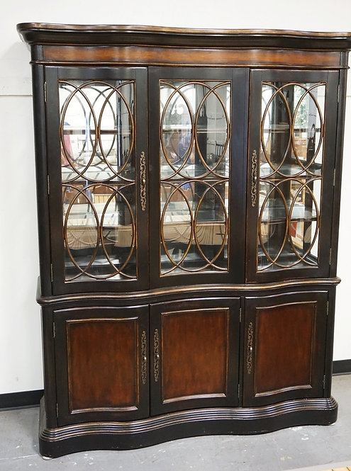 CHINA CABINET WITH A SERPENTINE FRONT. GLASS SHELVES, LIGHTED INTERIOR, AND A MI