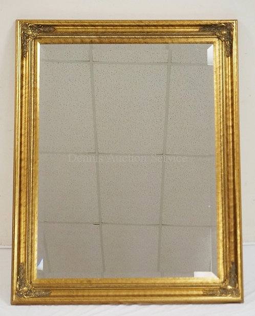 BEVELED GLASS WALL MIRROR WITH A GILD GILT FRAME. 38 X 48 INCHES.