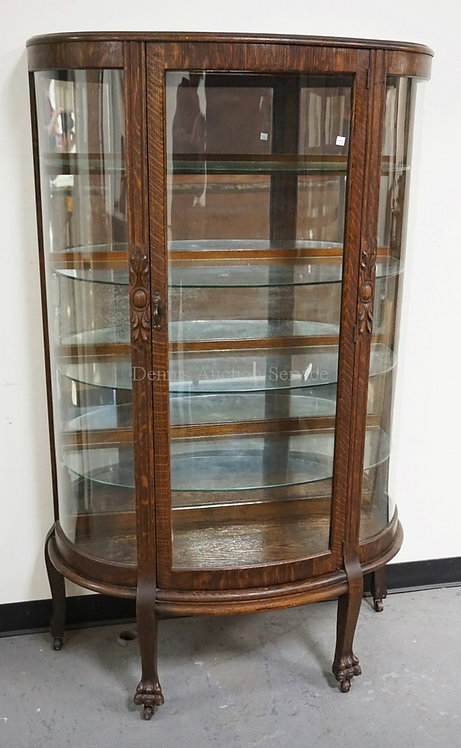 OAK CHINA CABINET WITH A MIRRORED BACK AND GLASS SHELVES. CARVED DECORATIONS INC