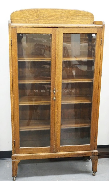 OAK BOOKCASE WITH 2 GLASS DOORS. 63 INCHES HIGH. 32 1/2 INCHES WIDE.