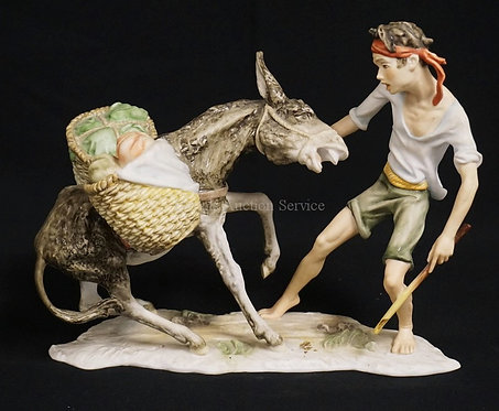 KAISER GERMAN PORCELAIN FIGURE OF A BOY TRYING TO LEAD A DONKEY. 8 INCHES HIGH.