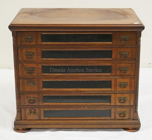 ANTIQUE SPOOL CABINET WITH 6 DRAWERS AND A LITHO DECORATED BACK DEPICTING A COUP