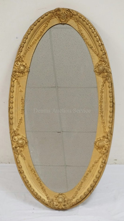OVAL MIRROR IN AN ORNATELY CARVED GOLD GILT FRAME. 47 X 24 3/4 INCHES.