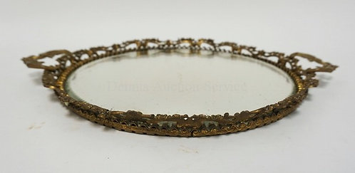MIRRORED TRAY WITH AN ORNATE BRONZE FRAME. 13 INCH DIA. THE MIRROR HAVING A BEVE