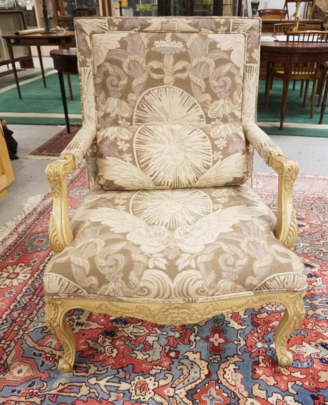 OVERSIZED CARVED AND UPHOLSTERED ARMCHAIR. 39 INCHES HIGH. 29 1/2 INCHES WIDE,