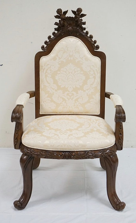 CARVED ARMCHAIR WITH A FULL RELIEF CREST OF CHERUBS. 45 1/2 INCHES HIGH. 26 INCH