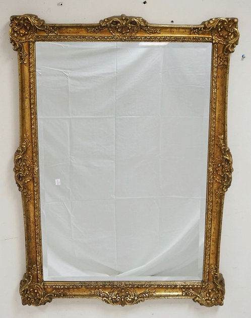 BEVELED MIRROR WITH AN ORNATE GOLD GILT FRAME. 30 X 42 INCHES.