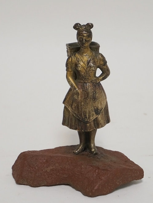 FIGURAL BRONZE MATCH HOLDER IN THE FORM OF A WOMAN WITH A BASKET ON HER BACK. TH