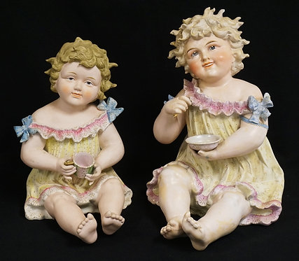 PAIR OF LARGE BISQUE PORCELAIN PIANO BABIES. TALLEST IS 13 3/4 INCHES.