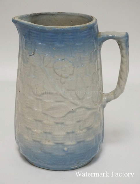 BLUE & WHITE GLAZED STONEWARE PITCHER WITH FLOWERS ON A BASKETWEAVE BACKGROUND.