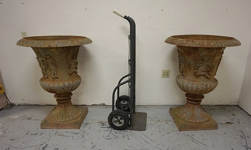 PAIR OF LARGE CAST IRON GARDEN URNS WITH RELIEF CHERUBS. 41 1/2 IN H, 32 IN TOP