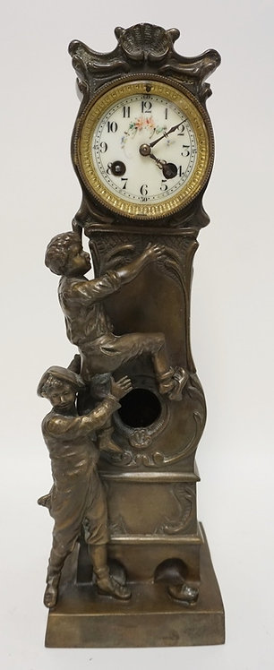 FIGURAL CLOCK DEPICTING 2 BOYS CLIMBING A GRANDFATHERS CLOCK. WHITE METAL WITH A