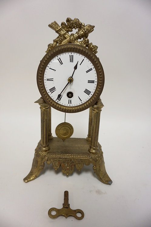 GILT METAL CLOCK WITH QUIVER AND TORCH CREST. SOME ENAMEL WEAR AROUND THE WINDER
