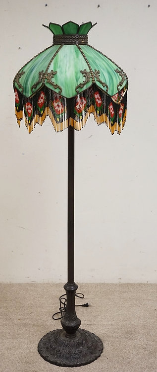 FLOOR LAMP WITH A CURVED SLAG GLASS SHADE HAVING BEADED FRINGE. 63 INCHES HIGH.