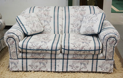 FLORAL UPHOLSTERED LOVESEAT MEASURING 66 INCHES LONG.