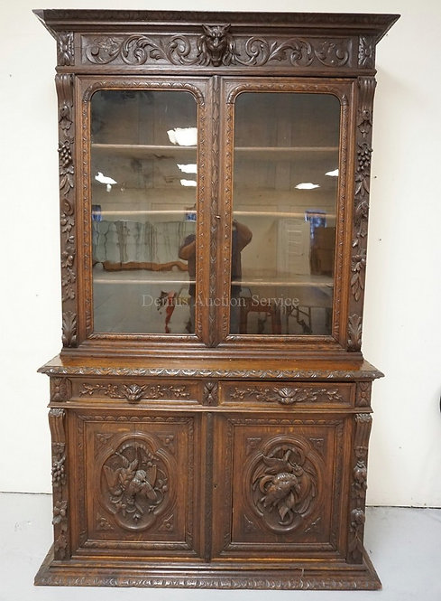 ORNATELY CARVED OAK SIDEBOARD WITH A BOOKCASE TOP. DECORATED WITH LION HEADS, FR
