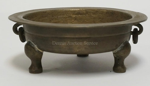 ASIAN BRONZE TRI FOOTED DISH WITH RING HANDLES. HAS A BAND OF CHARACTERS ON THE
