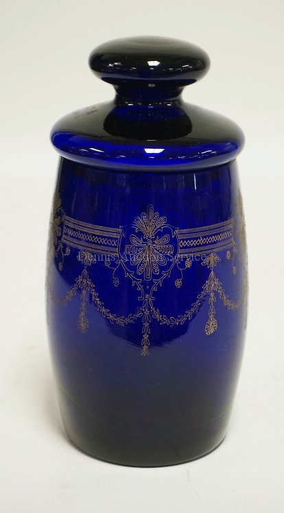 COBALT BLUE GLASS JAR WITH LID AND A GOLD TRIMMED ETCHED DECORATION. 9 INCHES HI