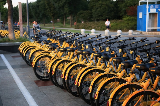 A row of yellow bicycles stand on the sidewalk, ready to be ridden.