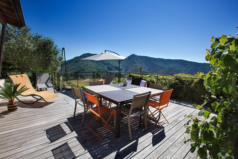 terrasse en bois , tables et chaises longues panorama sur l'Ardèche